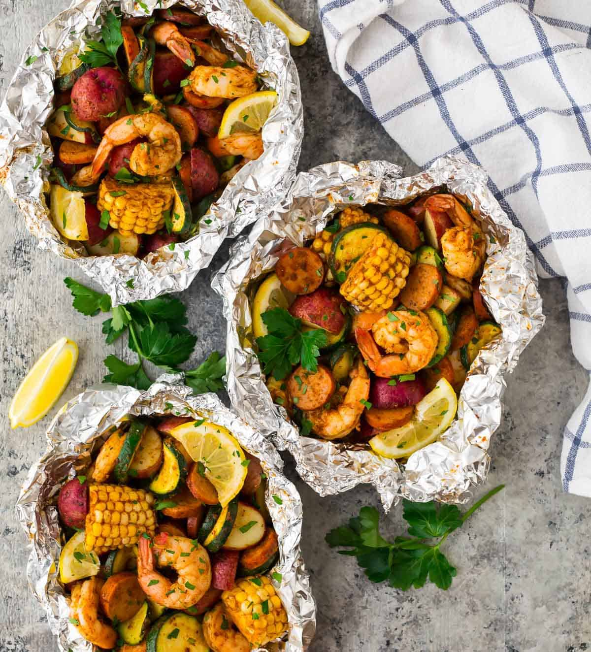 Three foil packets with Cajun shrimp, sausage, and vegetables with a blue striped towel and lemon wedge