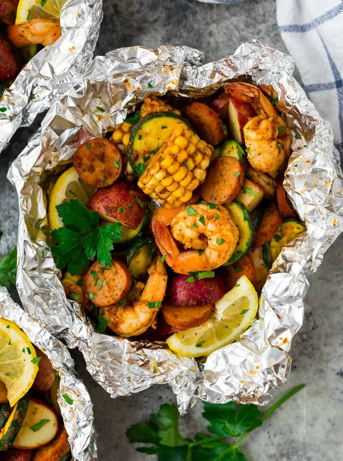 Cajun Shrimp Boil Foil Packets torn open with sausage, corn and zucchini