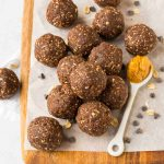 Healthy chocolate peanut butter energy balls on a wooden board