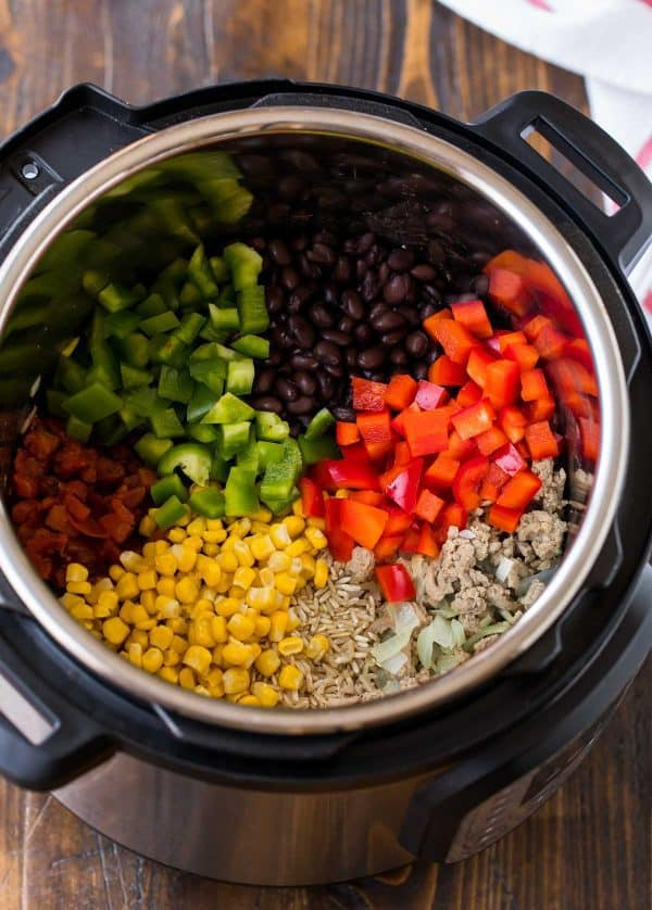 Healthy pressure cooker Mexican casserole with rice, bell peppers, ground chicken or turkey, tomatoes, and beans.