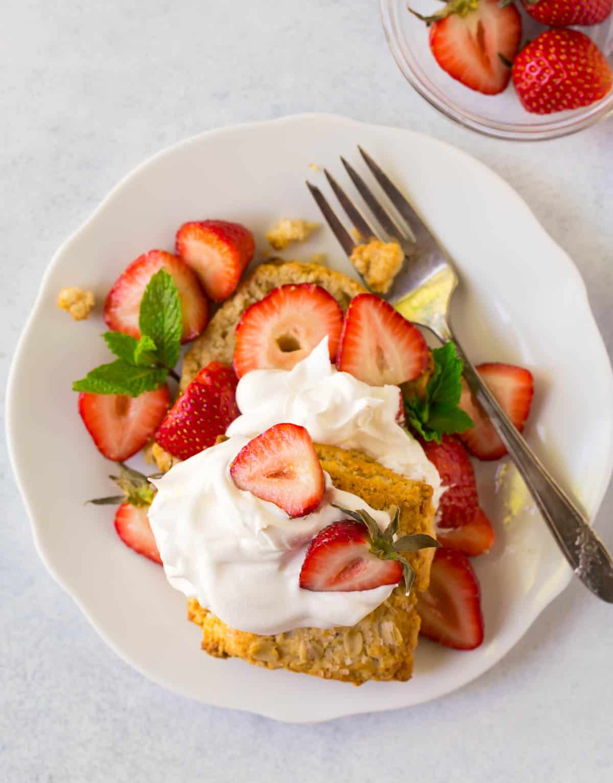 Gluten free strawberry shortcakes topped with whipped cream on a plate with a fork and a side of fresh strawberries