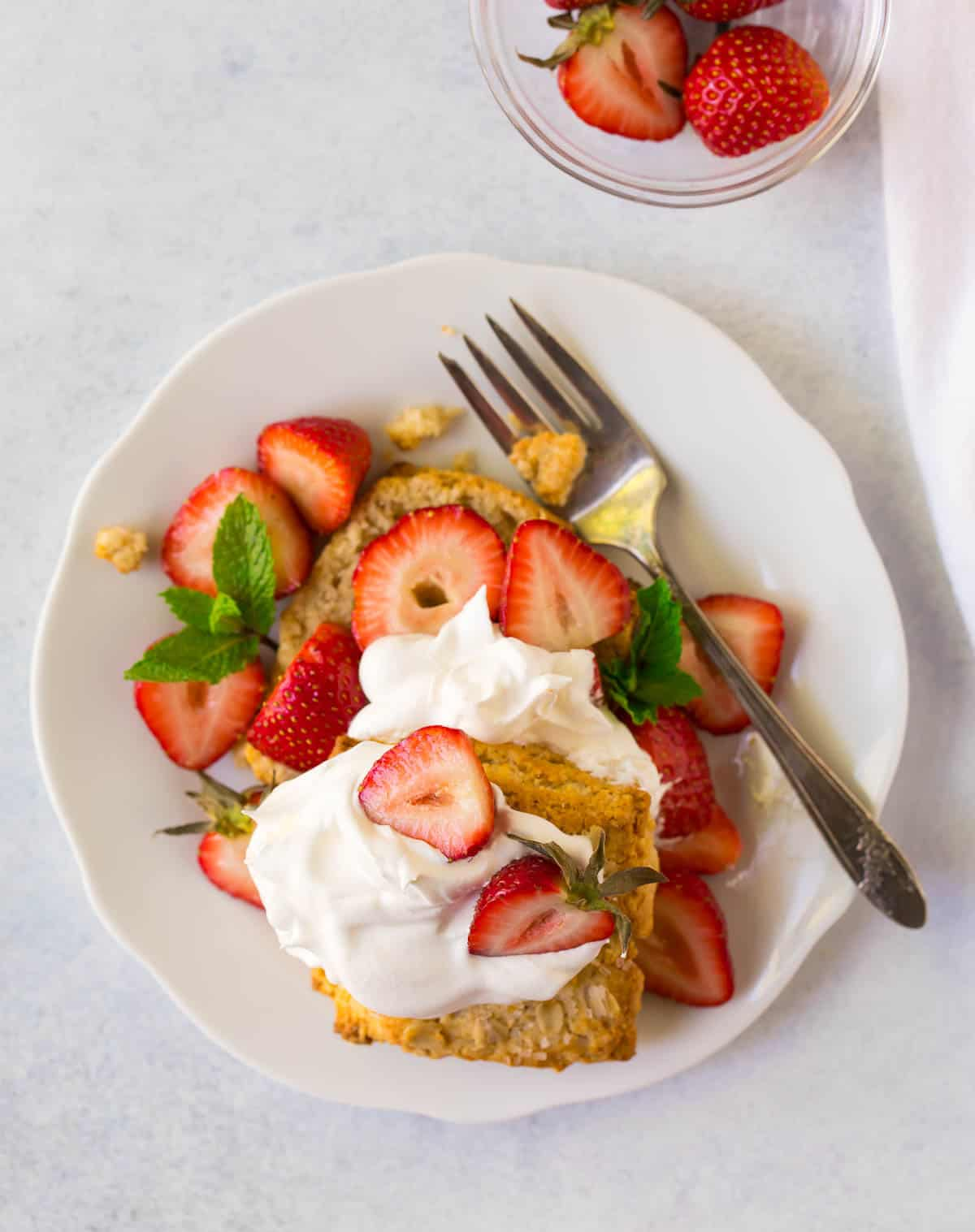 Overhead photo of gluten free strawberry shortcakes on a white plate with a fork and topped with fresh strawberries and whipped cream.