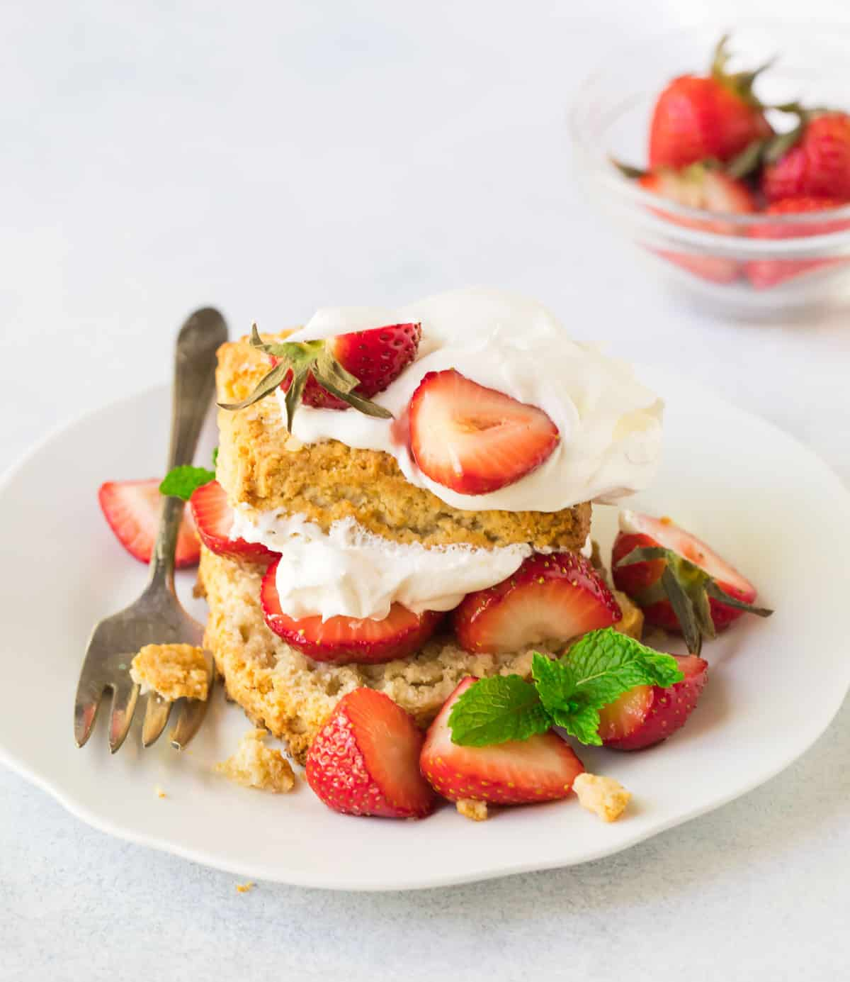 Tender, biscuit-style gluten free strawberry shortcakes made with oatmeal topped with whipped cream and berries on a white plate with a fork.