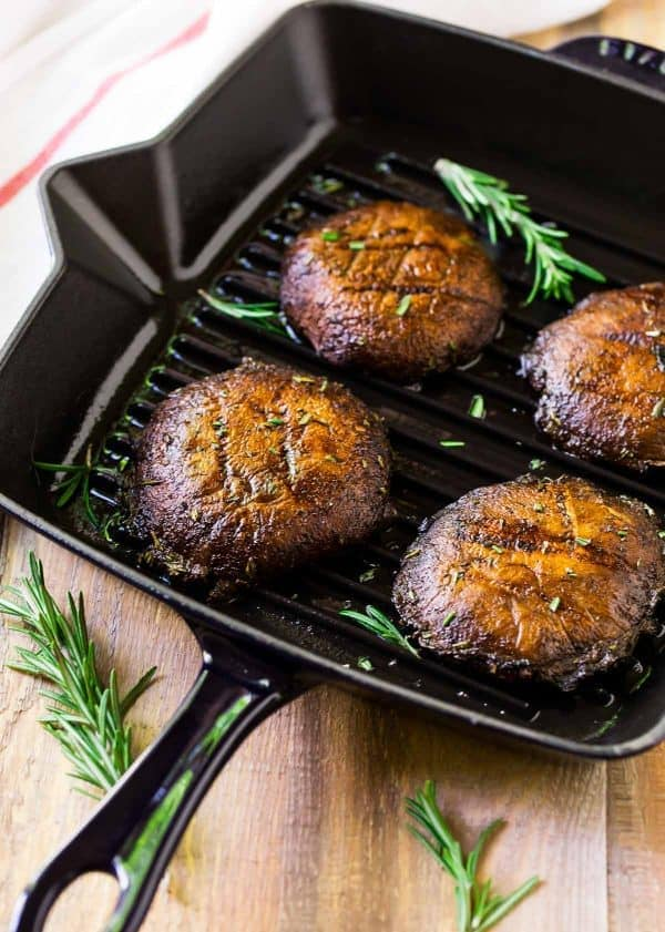 Grilled portobello mushrooms on a grill pan with fresh herbs