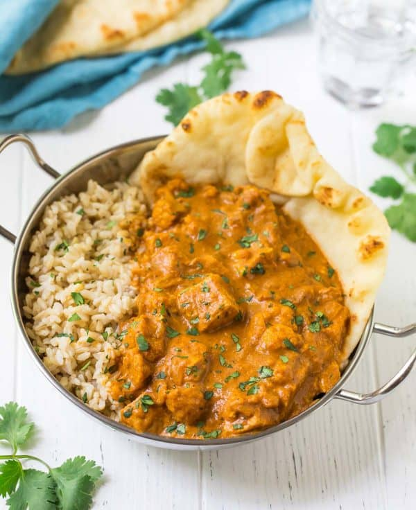 Butter chicken in a bowl with rice and naan