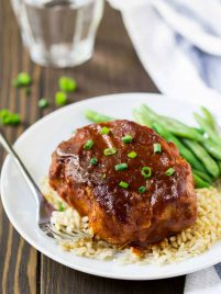 Crock pot pork chops on a plate with rice