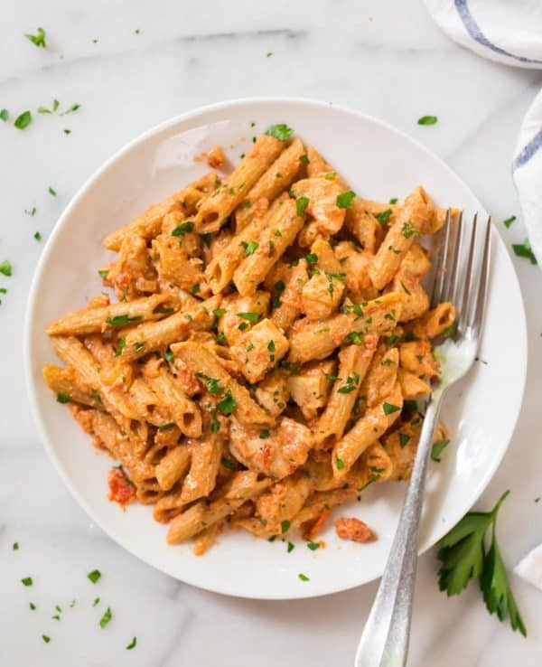 A fork resting on a plate of creamy penne alla vodka with chicken