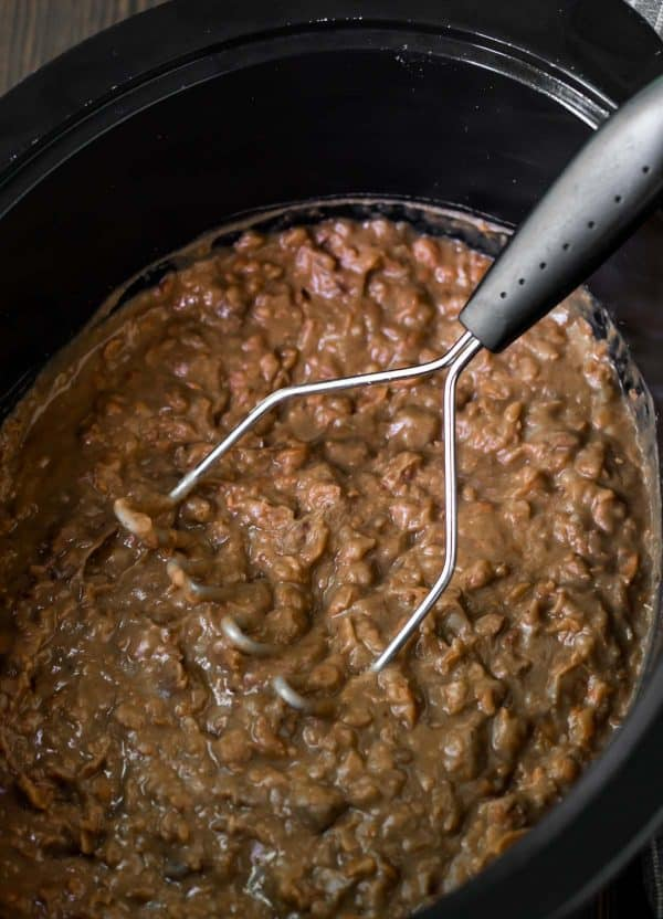 Mashed pinto beans in a slow cooker