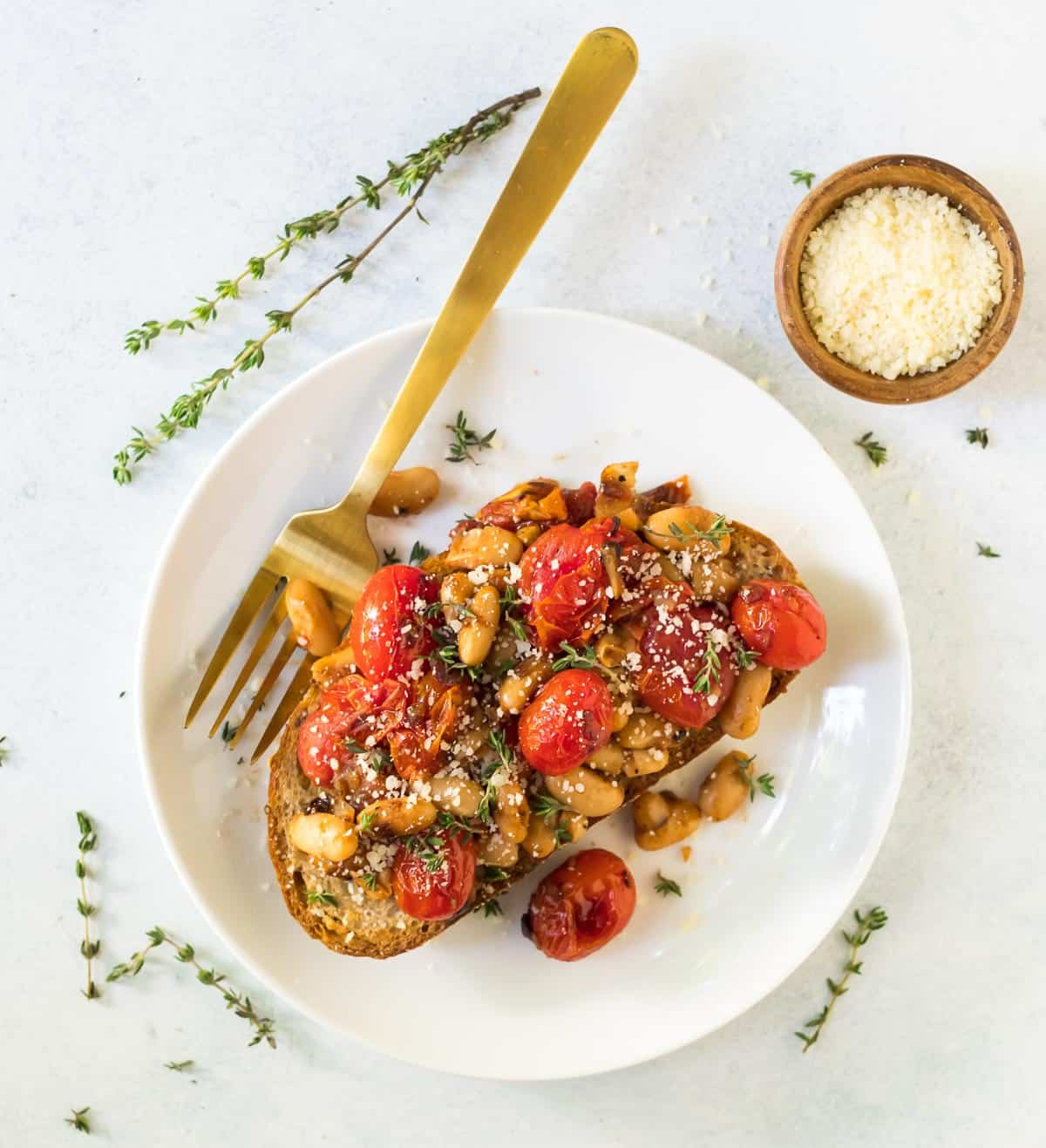 Simple and delicious Tuscan White Bean Tomato Toasts. Creamy white beans, bursting cherry tomatoes, olive oil, and garlic, served over toasted bread. A fast and easy, filling vegetarian recipe that's great for easy, healthy, and budget friendly lunches and dinners!