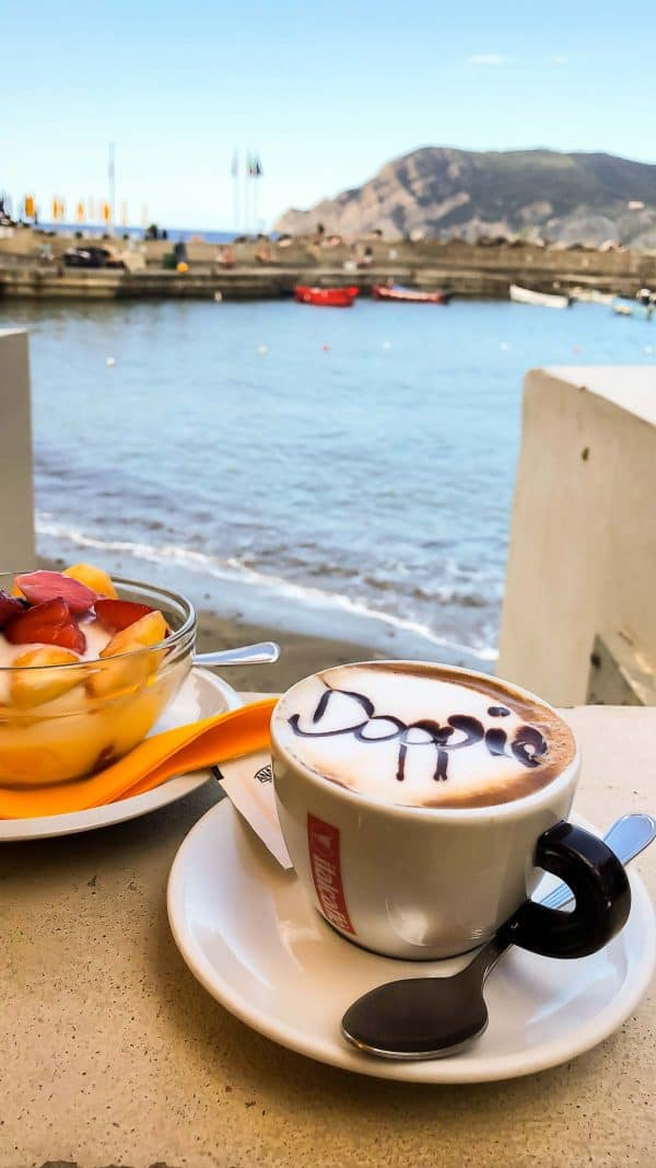 A cup of coffee and a bowl of fruit on a table next to the ocean