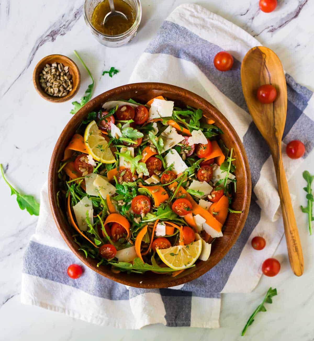 A bowl of arugula salad with tomatoes, carrots, and Parmesan