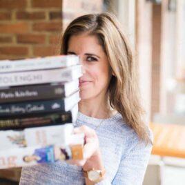 Erin Clarke holding a stack of cookbooks