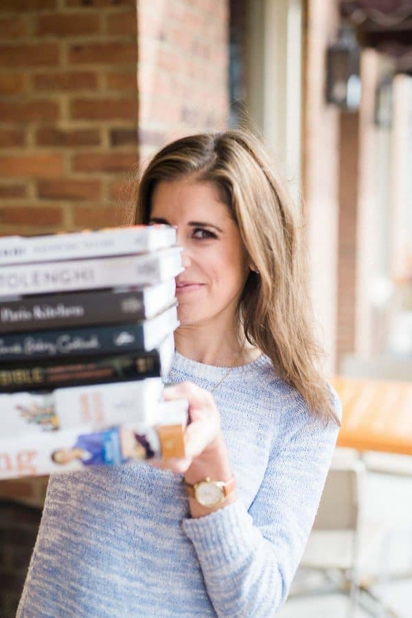 Erin Clarke holding a stack of cookbooks