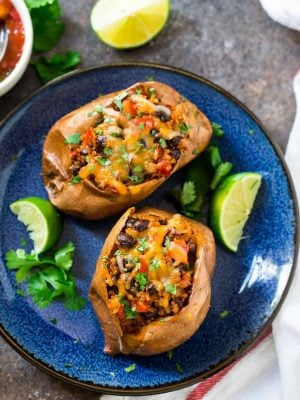 Healthy Southwest Stuffed Sweet Potatoes with Black Beans and Quinoa. A protein packed, delicious vegetarian recipe! Flavorful, not too spicy, and great for meatless meals. These savory stuffed sweet potatoes are easy, budget-friendly, and can be baked in advance for meal prep lunches and dinners!
