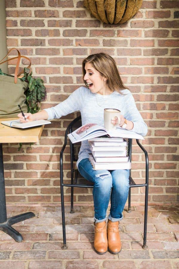Erin Clarke sitting on a chair with a stack of cookbooks