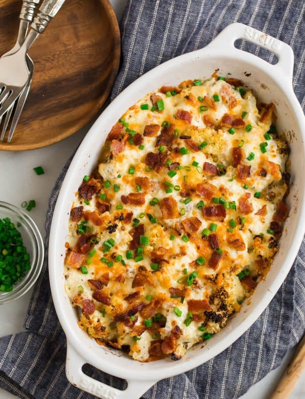 Loaded cauliflower casserole served in a baking dish with chives and bacon