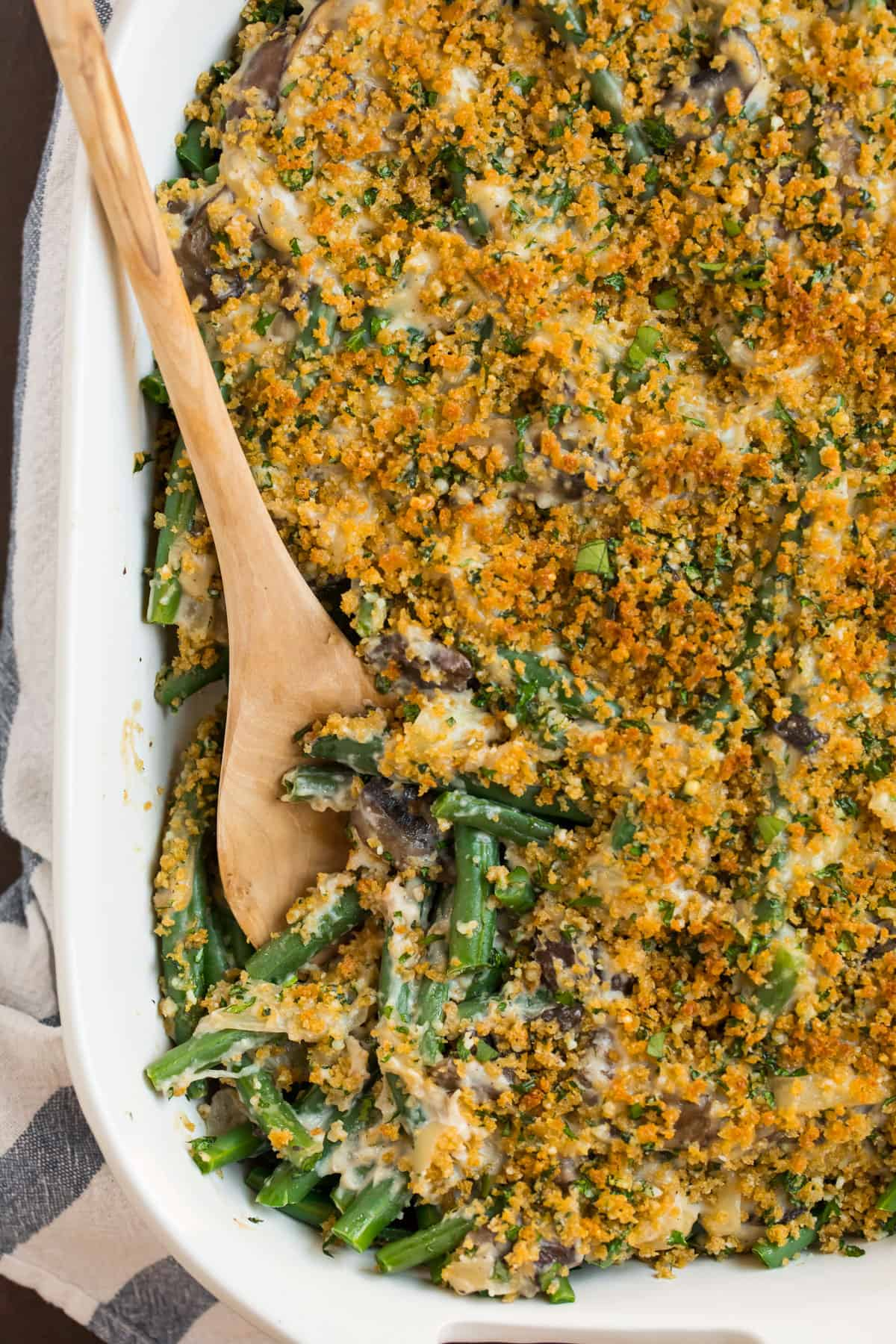 Healthy green bean casserole with cheese and breadcrumbs in a baking dish