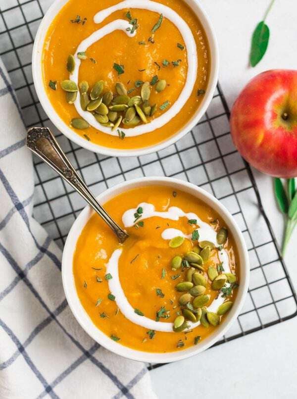 Healthy vegan recipe for the BEST Crockpot Butternut Squash Soup with coconut milk and apple. The crock pot makes it easy and it tastes better than Panera! Rich, creamy, and made with simple ingredients, this is one of the best fall comfort foods.