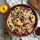 Crisp Winter Slaw with dried cranberries, cabbages, apple, and Parmesan. A healthy, fresh, and delicious coleslaw recipe that's perfect for a Christmas or Thanksgiving side dish. Add chicken or quinoa to make it easy to pack for lunch! Lasts in the refrigerator for several days, so it's great as a make ahead side or for meal prep.