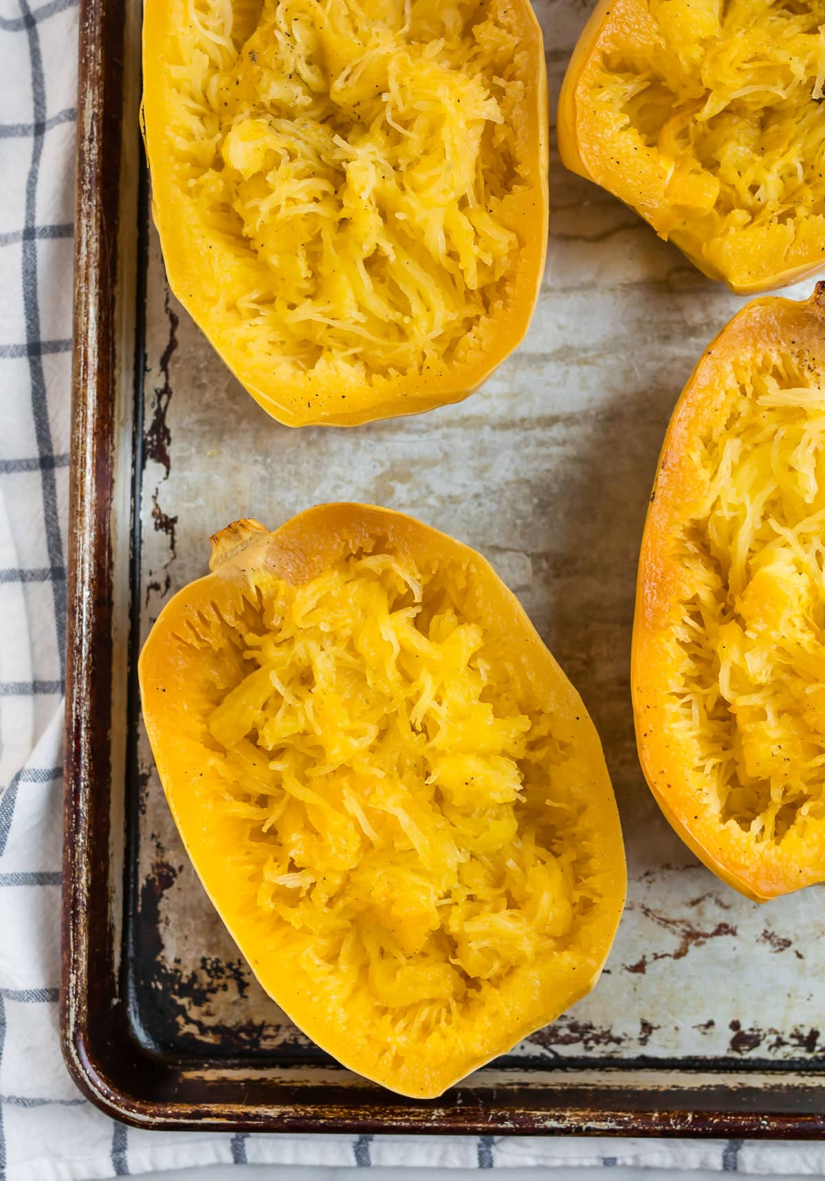 Spaghetti squash halves on a baking sheet