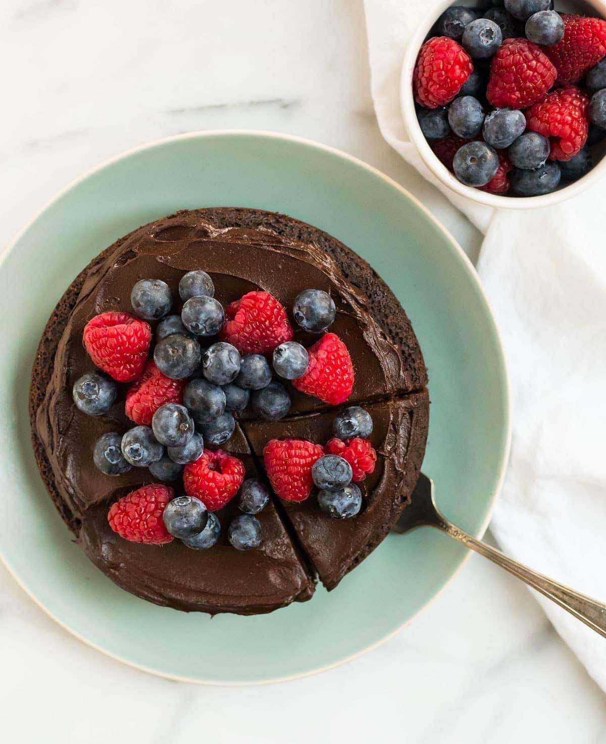 Instant Pot cake on a blue plate with fresh berries on top