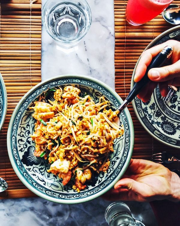 A blue bowl of pad thai and how travel inspires recipe development
