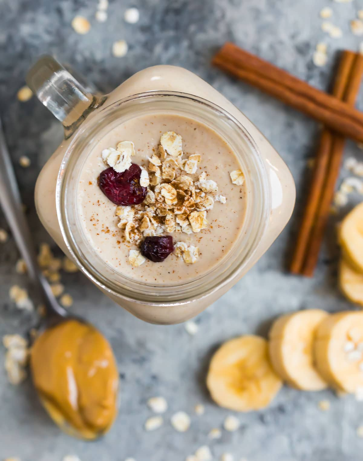 An oatmeal smoothie next to a spoon with peanut butter, bananas, and cinnamon sticks