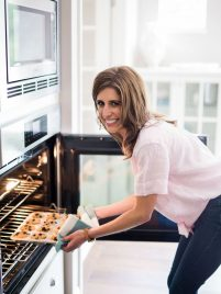 Erin placing muffins in the oven