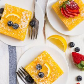 Three pieces of lemon poke cake on white plates