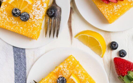 Three pieces of lemon poke cake on white plates