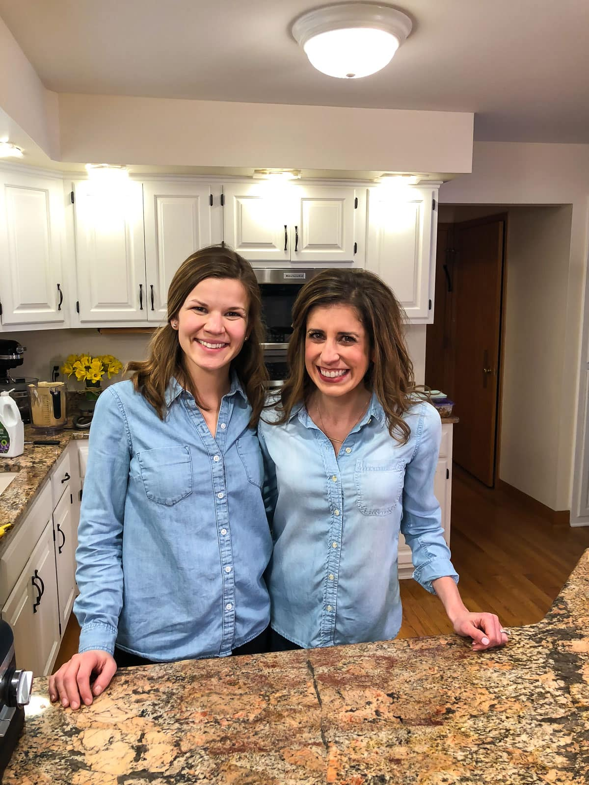 Two girls in chambray shirts standing in a white kitchen