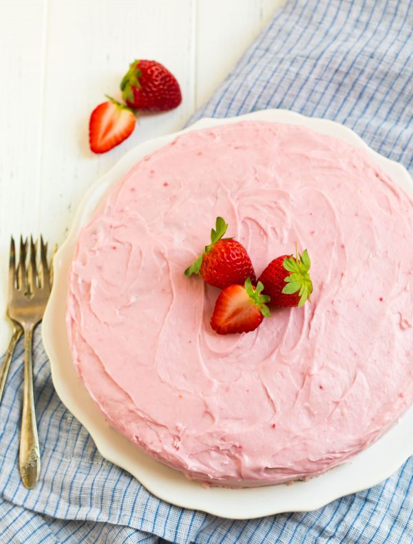 A pink and moist dessert served on plate with fresh fruit