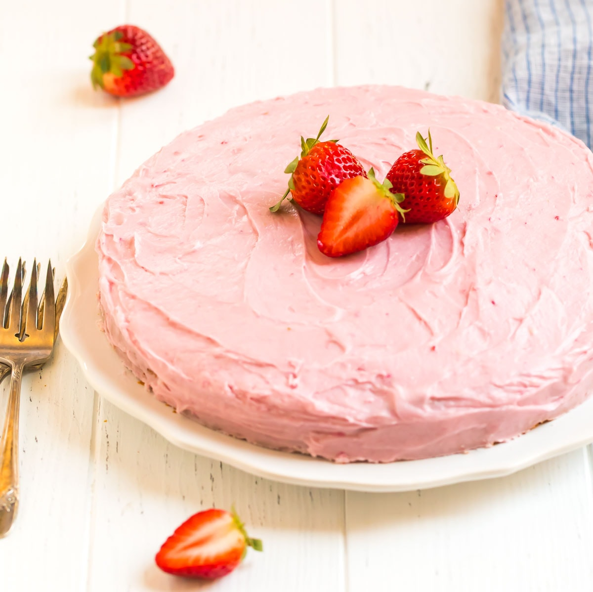 A beautiful and simple cake served on a plate with fresh fruit
