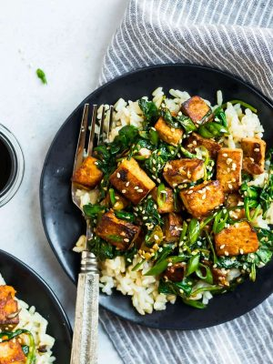 Easy Sesame Tofu Stir Fry. Crispy tofu with spinach, broccoli, or any fresh vegetables you love. This vegan recipe is packed with flavor in a simple, delicious Asian garlic ginger sauce. Serve with rice or noodles.