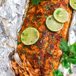 Spicy baked salmon in aluminum foil with lime slices