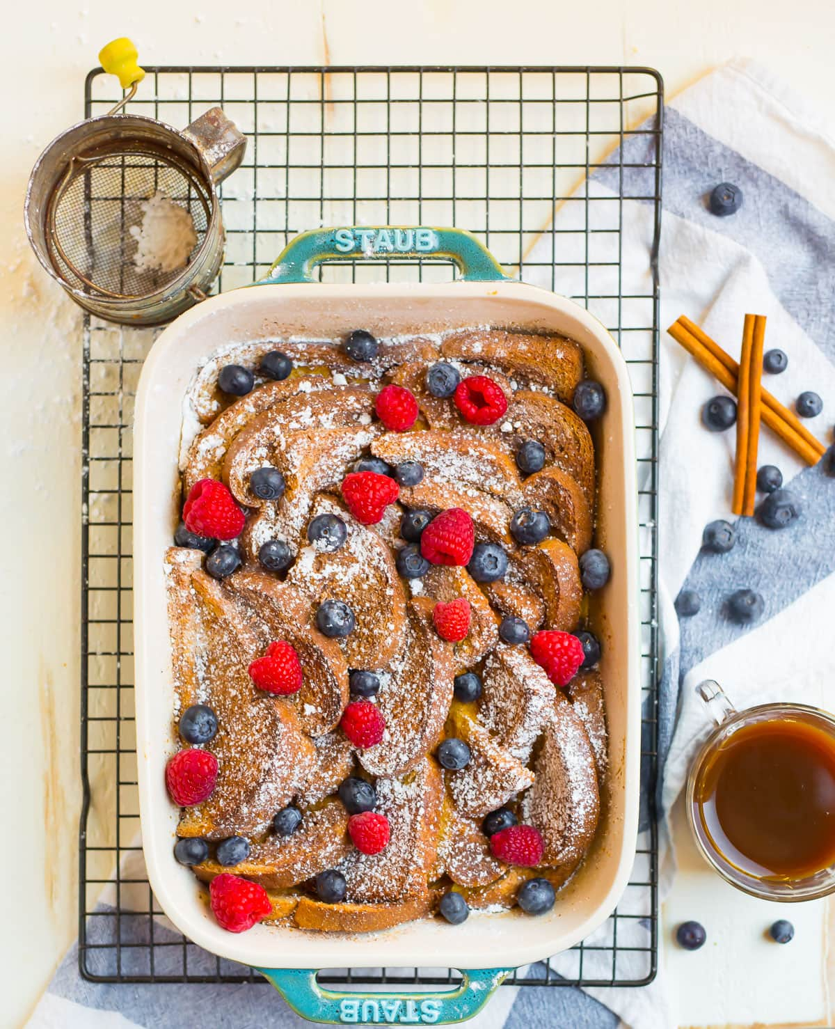 A pan of French toast casserole sprinkled with powdered sugar