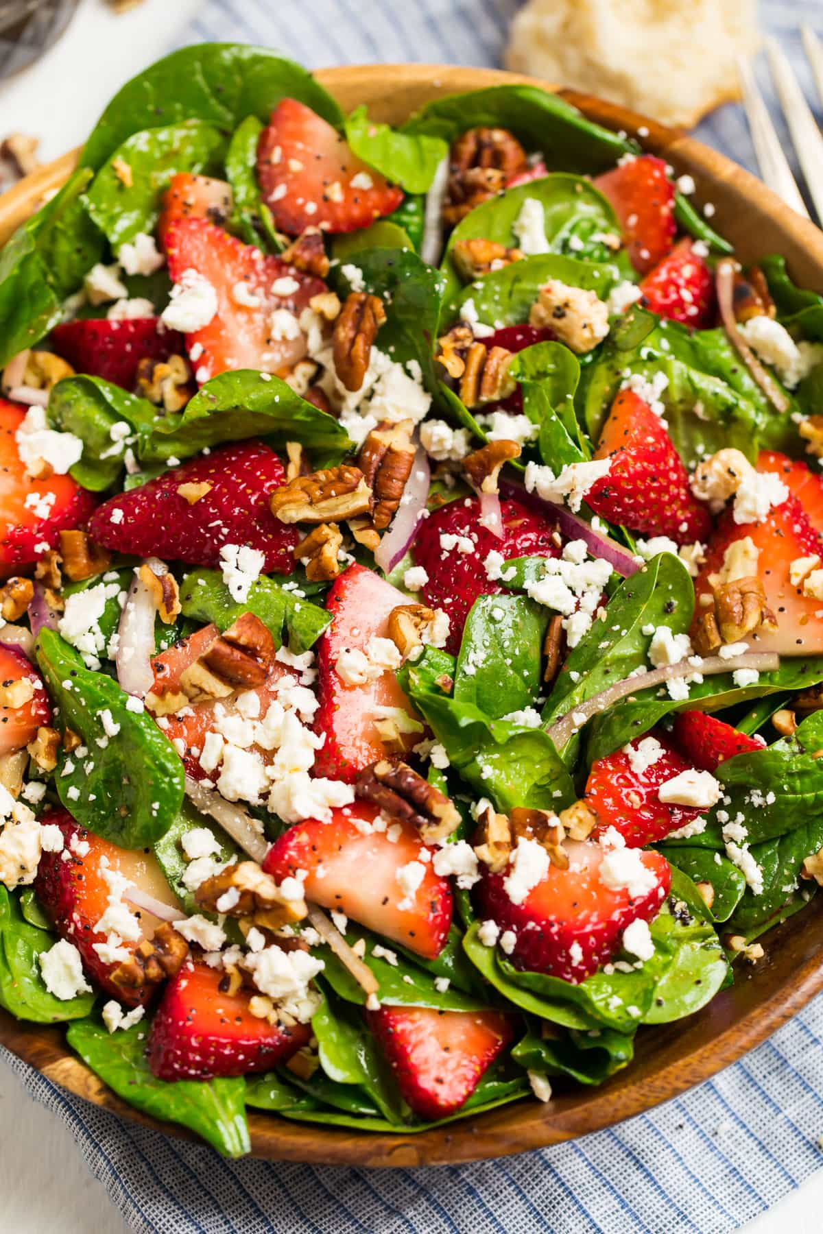 A bowl full of spinach salad with strawberries, feta, pecans, and poppy seeds