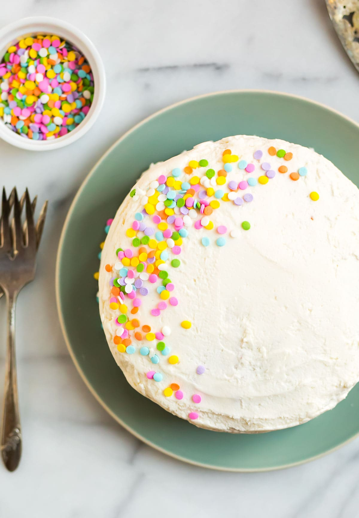 A white coconut flour layer cake with rainbow sprinkles