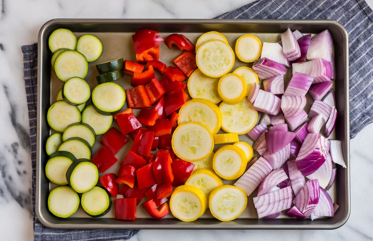 Zucchini, red bell pepper, squash, and red onion on a baking sheet