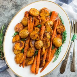 Perfecto asado de patatas y zanahorias con romero en una placa blanca.