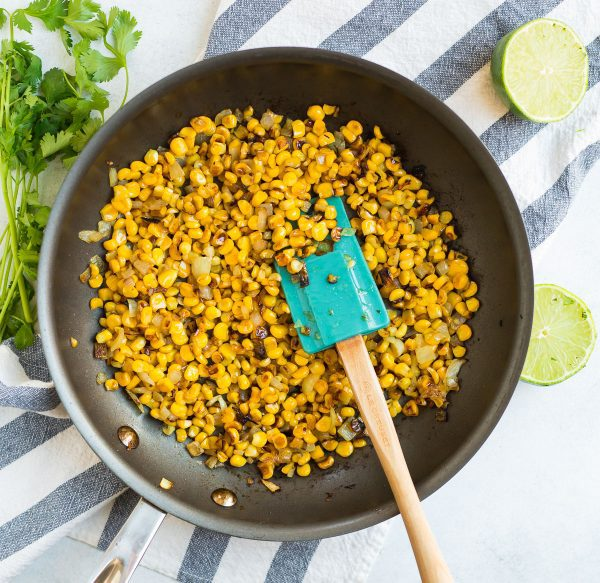 A skillet with corn kernels for Mexican Street Corn Quinoa Salad