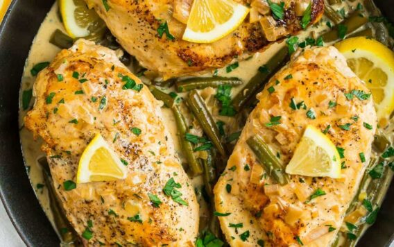 A skillet with three chicken breasts in a lemon butter sauce