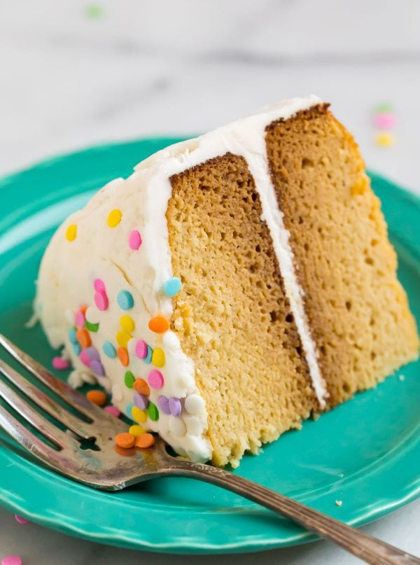 A slice of moist Coconut Flour cake with frosting and sprinkles