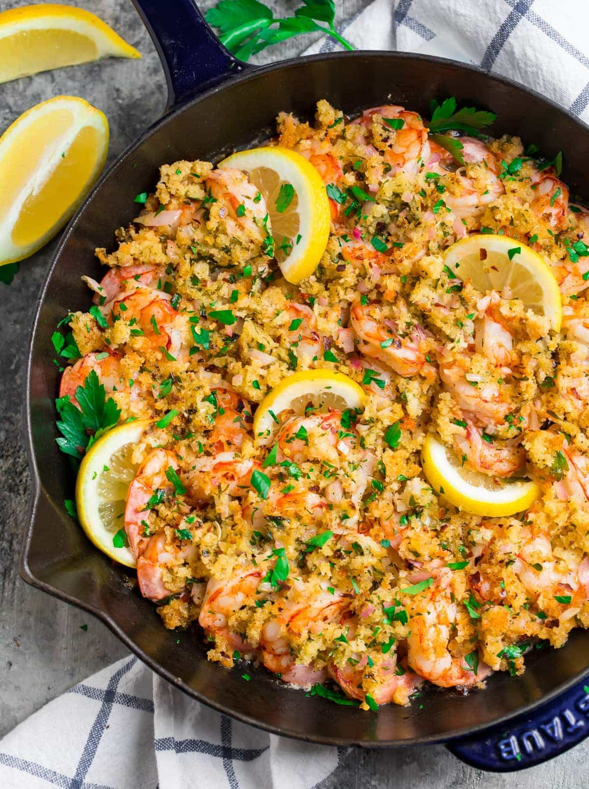 A skillet with baked shrimp scampi topped with garlic butter bread crumbs, lemon slices, and fresh parsley