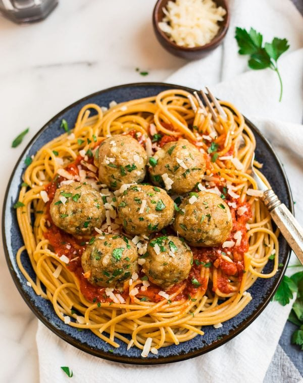 A plate of Baked Turkey Meatballs served with whole wheat pasta and tomato sauce