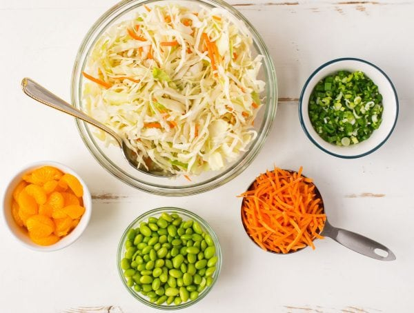 Ingredients for Ramen Salad, including cabbage, carrots, edamame, and mandarin oranges