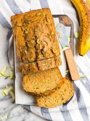 A loaf of moist zucchini banana bread with slices cut