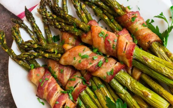 A white plate with bacon wrapped asparagus spears