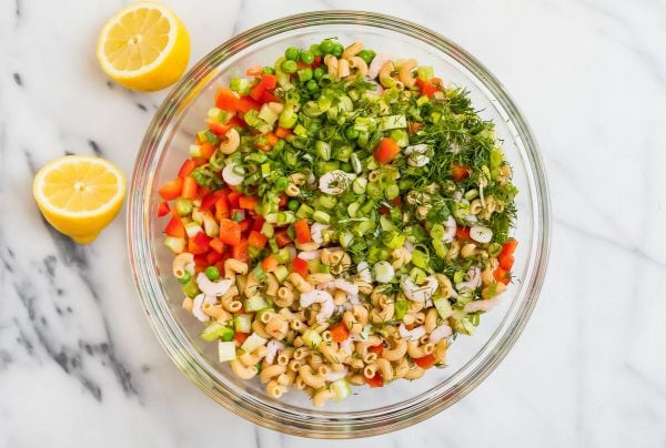 A clear bowl with ingredients for Shrimp Pasta Salad