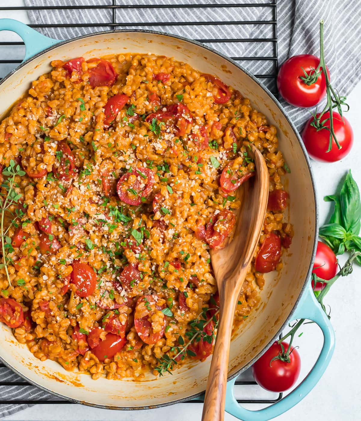 A pan of Farro Risotto on a cooling rack with burst cherry tomatoes and a wooden spoon